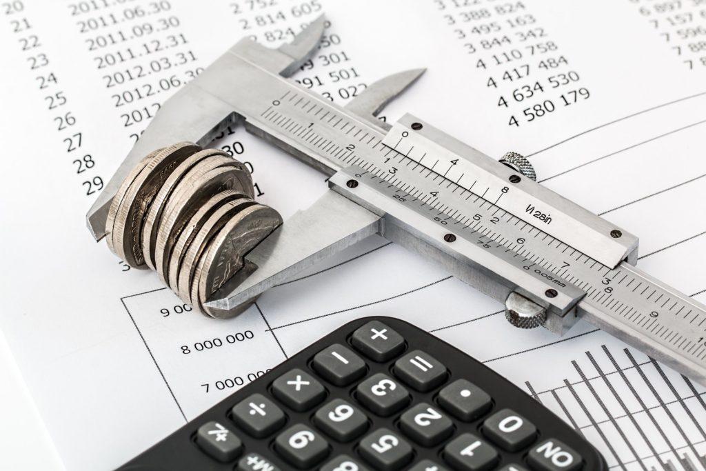 calculadora com tabela de custos e medidor com várias moedas simbolizando redução de orçamento