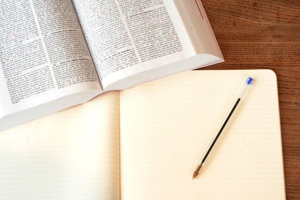 Livro aberto e um caderno em branco com uma caneta azul em cima.